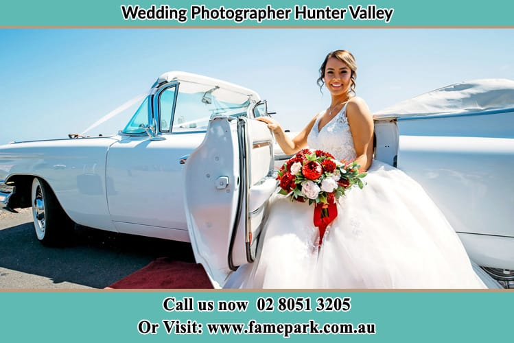 Photo of happy bride to be getting out of vintage white car Hunter Valley