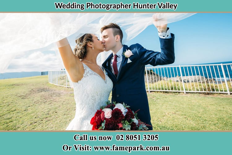 Photo of bride and groom kissing in a field Hunter Valley